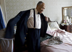 Eugene Allen, 89, who worked under eight presidents from 1952 to 1986, tries on his old White House uniform last week for a photographer. (Kevin Clark -- The Washington Post)