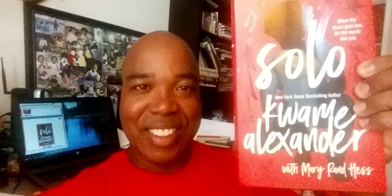Kwame Alexander's book Solo held by Troy Johnson